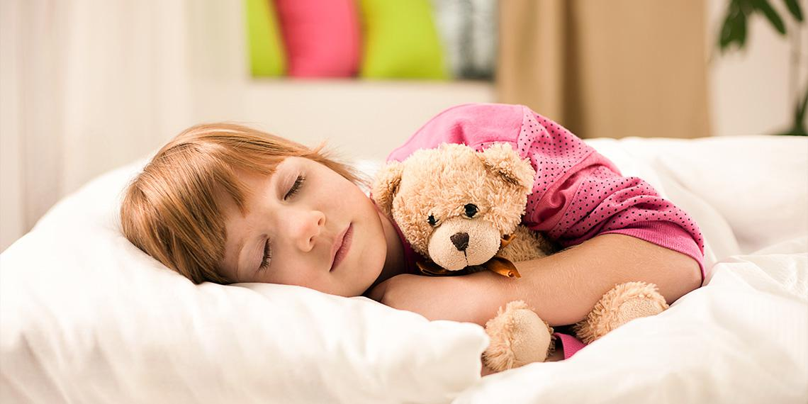 red hair little girl sleeping in bed